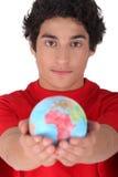 Adolescente que sostiene un mini globo Imagen de archivo