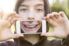 Adolescente que sostiene un teléfono elegante Fotografía de archivo