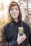 Adolescente que sostiene un teléfono elegante delante de su corazón Fotografía de archivo