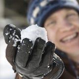 Adolescente que sostiene una bola de nieve. Imagen de archivo libre de regalías