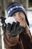 Adolescente que sostiene una bola de nieve. Fotografía de archivo