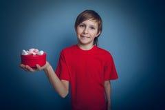 Adolescente que sostiene una caja roja de Europeo-mirada adentro Foto de archivo
