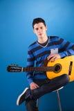 Adolescente que sostiene una guitarra clásica Foto de archivo libre de regalías