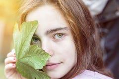 Adolescente que sostiene una hoja de arce Imagen de archivo libre de regalías