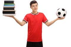 Adolescente que sostiene una pila de libros y de un fútbol Fotografía de archivo
