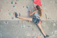 Adolescente que sube una pared de la roca Foto de archivo libre de regalías
