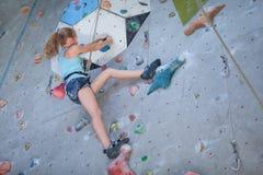 Adolescente que sube una pared de la roca Fotos de archivo libres de regalías