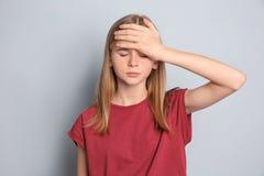 Adolescente que sufre de dolor de cabeza en fondo gris Imagen de archivo