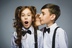 Adolescente que susurra en el oído de la muchacha adolescente en un fondo gris Emoción humana positiva, expresión facial primer Fotos de archivo