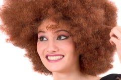 Adolescente que tem o divertimento com peruca curly Imagem de Stock