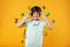 Adolescente que tem o divertimento e que pressiona dois dispositivos a suas orelhas imagens de stock royalty free