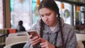 Adolescente que texting no smartphone que senta-se no café vídeos de arquivo