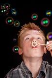 Adolescente que tiene burbujas de jabón de la diversión que soplan Foto de archivo