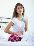 Adolescente que tiene dolor del vientre y que toma píldoras Imagen de archivo