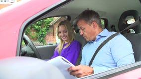 Adolescente que tiene lección de conducción con el instructor almacen de metraje de vídeo