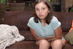 Adolescente que tiene un dolor de estómago que se sienta en el sofá en su hogar Imagenes de archivo