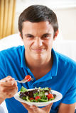 Adolescente que tira de la cara mientras que come la ensalada sana Imagen de archivo libre de regalías