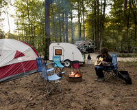 Adolescente que toca la guitarra en camping Imagen de archivo
