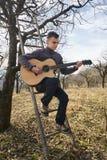 Adolescente que toca la guitarra en el campo Imagenes de archivo