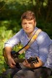 Adolescente que toca la guitarra en el parque Imagen de archivo