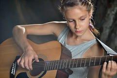 Adolescente que toca la guitarra en la calle Imágenes de archivo libres de regalías