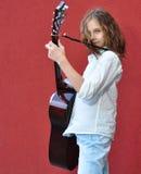 Adolescente que toca la guitarra en la calle Imagen de archivo libre de regalías