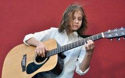 Adolescente que toca la guitarra en la calle Imagenes de archivo