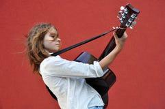 Adolescente que toca la guitarra en la calle Fotos de archivo