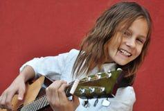 Adolescente que toca la guitarra en la calle Foto de archivo libre de regalías