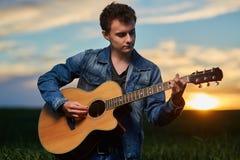 Adolescente que toca la guitarra en la puesta del sol Imágenes de archivo libres de regalías