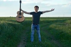 Adolescente que toca la guitarra en la puesta del sol Foto de archivo