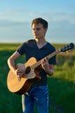 Adolescente que toca la guitarra en la puesta del sol Foto de archivo libre de regalías