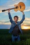 Adolescente que toca la guitarra en la puesta del sol Fotografía de archivo libre de regalías