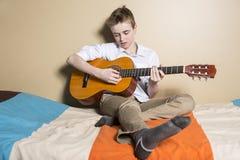 Adolescente que toca la guitarra en su dormitorio Fotos de archivo