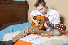 Adolescente que toca la guitarra en su dormitorio Imágenes de archivo libres de regalías