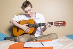 Adolescente que toca la guitarra en su dormitorio Imagenes de archivo