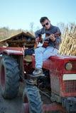 Adolescente que toca la guitarra en un tractor Fotos de archivo libres de regalías