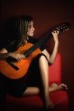Adolescente que toca una guitarra acústica Imagen de archivo libre de regalías