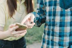 Adolescente que toca una pantalla de un smartphone Fotos de archivo