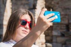 Adolescente que toma el autorretrato con su teléfono elegante Foto de archivo libre de regalías