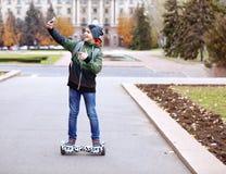 Adolescente que toma el selfie mientras que monta en gyroscooter Imágenes de archivo libres de regalías
