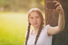 Adolescente que toma el selfie usando el teléfono móvil adentro Imagen de archivo