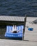 Adolescente que toma el sol en el lago Imagen de archivo libre de regalías