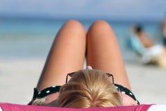 Adolescente que toma el sol en la playa Foto de archivo libre de regalías