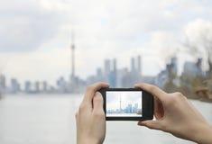 Adolescente que toma a foto la opinión hermosa del horizonte del centro de la ciudad de Toronto con el teléfono celular Imagen de archivo