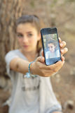 Adolescente que toma las fotos con su móvil Imagen de archivo