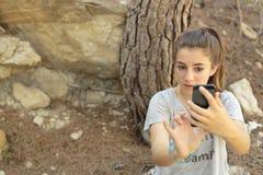 Adolescente que toma las fotos con su móvil Fotografía de archivo libre de regalías