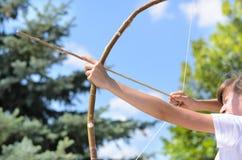 Adolescente que toma objetivo con un arco y una flecha Fotos de archivo