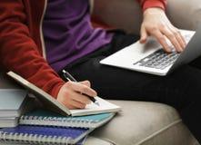 Adolescente que trabaja con el ordenador portátil mientras que hace lecciones Imagenes de archivo