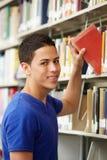 Adolescente que trabaja en biblioteca Foto de archivo